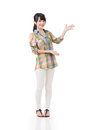 Young asian woman shows or introduce something with hands on the white space full length portrait isolated on the white background Stock Images
