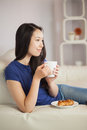 Young asian woman sitting on the sofa having coffee with a pastr pastry in living room at home Stock Photo
