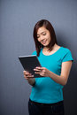 Young asian woman smiling as she reads a tablet pretty stands reading computer in front of dark studio background Royalty Free Stock Images