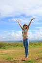 Young asian woman standing in field and rising up her hand with nice emotion Royalty Free Stock Photo