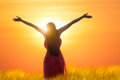 Young asian woman standing open her arms under the sunrise Royalty Free Stock Photo