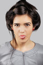 Young asian woman sticking out her tongue out grey background Stock Images