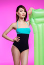Young asian woman in swimsuit posing with swimming mattress and looking at camera Royalty Free Stock Photo