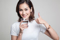 Young Asian woman thumbs up with a glass of drinking water. Royalty Free Stock Photo