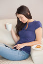 Young asian woman using her tablet pc and holding mug of coffee in sitting room at home Stock Images