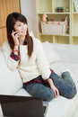 Young asian woman using a laptop and cellphone at home Stock Image