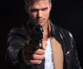 Young assasin pointing his gun to the camera closeup picture of a on dark background Royalty Free Stock Photography