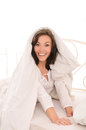 Young astonished woman covered with blanket on white bed in light bedroom Royalty Free Stock Images