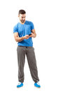 Young athlete in sport outfit using smart phone full body length portrait isolated over white background Stock Image