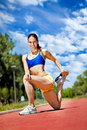 Young athlete woman exercising and stretching on sport track Royalty Free Stock Photos