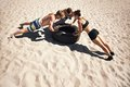 Young athletes doing push ups on tire small group of people working out beach during a hot summer day Royalty Free Stock Images