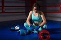 Young athletic female boxer sitting near lying boxing gloves and Royalty Free Stock Photo