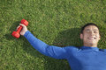 Young athletic man lying down in grass with dumbbells directly above view Royalty Free Stock Image