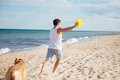 Young athletic man playing with his dog on the beach Royalty Free Stock Photo