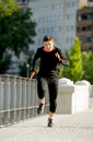 Young athletic man running on urban city park in sport training session practicing sprinting background summer body and health Stock Photo