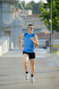 Young athletic man running on urban city park in summer sport training session happy with sunglasses practicing background body Stock Images