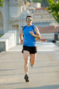 Young athletic man running on urban city park in summer sport training session happy with sunglasses practicing background body Stock Image