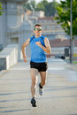 Young athletic man running on urban city park in summer sport training session with sunglasses practicing background body and Royalty Free Stock Images