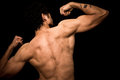 Young athletic shirtless man posing on black background is and flexing his arms Royalty Free Stock Photography