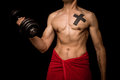 Young athletic shirtless man working out on black background is with a dumbbell Royalty Free Stock Image