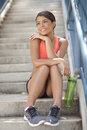 Young athletic woman smilling beautiful in clothes sitting on steps smiling Royalty Free Stock Images