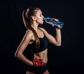 Young athletic woman in sportswear drinking water in studio against black background. Ideal female sports figure. Royalty Free Stock Photo