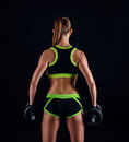 Young athletic woman in sportswear with dumbbells in studio against black background. Ideal female sports figure. Fitness girl wit Royalty Free Stock Photo