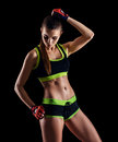 Young athletic woman in sportswear posing in studio against black background. Ideal female sports figure. Royalty Free Stock Photo