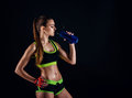 Young athletic woman in sportswear with a shaker in studio against black background. Ideal female sports figure. Royalty Free Stock Photo
