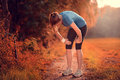 Young athletic woman taking a break from training standing resting her hands on her knees on rural track through lush farmland Royalty Free Stock Photo