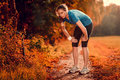 Young athletic woman taking a break from training standing resting her hands on her knees on rural track through lush farmland Royalty Free Stock Images