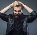 Young attractive bearded hipster man gesturing emotional screaming in studio sucsess. fashion modern guy Royalty Free Stock Photo