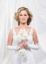 A young and attractive blond bride in a white dress beautiful standing holding flower bouquet the image is taken on light silk Royalty Free Stock Photo