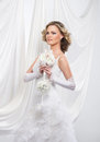 A young and attractive blond bride in a white dress beautiful standing holding flower bouquet the image is taken on light silk Stock Photography