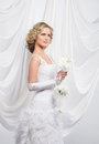 A young and attractive blond bride in a white dress beautiful standing holding flower bouquet the image is taken on light silk Royalty Free Stock Images