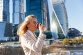 Young attractive blond woman in beige jacket drinking coffee outdoors Royalty Free Stock Photo