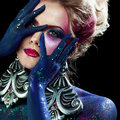 Young attractive blonde girl in bright art-makeup, high hair, body painting. Rhinestones and glitter Royalty Free Stock Photo
