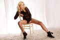 Young attractive blonde girl sitting on chair posing fashionable photo of beautiful sexy woman looking at camera Royalty Free Stock Photo