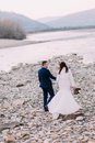 Young attractive bridal couple walking on pebble riverside with forest hills as background. Back view Royalty Free Stock Photo