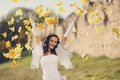 Young attractive bride outdoor throws yellow leaves Stock Photo