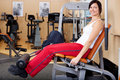 Young attractive brunette woman in the gym doing leg strengthening exercises Royalty Free Stock Photo