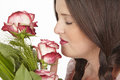 Young attractive brunette woman smells at roses Royalty Free Stock Photo