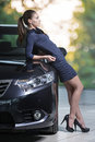 Young attractive brunette woman standing next to luxury car good looking female fashion model wearing dark blue color dress and Royalty Free Stock Photography