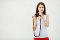 Young attractive brunette woman in white t shirt posing with a photo camera against textured wall Royalty Free Stock Image