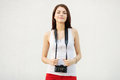 Young attractive brunette woman in white t shirt posing with a photo camera against textured wall Royalty Free Stock Images