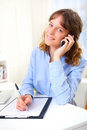 Young attractive business woman copying data on paper while phoning Royalty Free Stock Photos