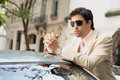 Young attractive businessman leaning top car classic street wearing sunglasses Stock Image
