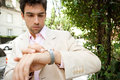Young attractive businessman looking at the time in his watch while standing in a classic city street outdoors Royalty Free Stock Image
