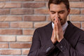 Young attractive businessman portrait of in classical suit keeping hands like praying standing against brick wall Royalty Free Stock Photography