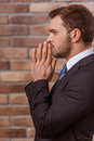 Young attractive businessman side view of in classical suit keeping hands like praying standing against brick wall Stock Photo